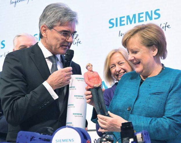Bundeskanzlerin Angela Merkel (CDU) betrachtet eine Merkel-Figur aus dem 3-D-Drucker neben Joe Kaeser, Vorstandsvorsitzender von Siemens, am 24.04.2017 am Stand von Siemens beim Eröffnungsrundgang zur Hannover Messe auf dem Messegelände in Hannover (Niedersachsen). Zur weltgrößten Industriemesse Hannover Messe vom 24. bis 28. April werden 6500 Aussteller erwartet. Partnerland ist im Jahr 2017 Polen. Foto: Julian Stratenschulte/dpa Foto: Julian Stratenschulte/dpa +++(c) dpa - Bildfunk+++